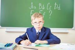 Lo scolaro si siede ad uno scrittorio all'aula della scuola Immagine Stock Libera da Diritti