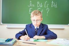 Lo scolaro si siede ad uno scrittorio all'aula della scuola Immagine Stock