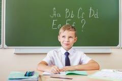 Lo scolaro si siede ad uno scrittorio all'aula della scuola Fotografie Stock Libere da Diritti