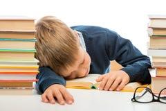 Lo scolaro sta dormendo ad una tavola fra i mucchi dei libri su un whi Fotografia Stock Libera da Diritti