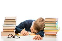 Lo scolaro stanco sta dormendo ad una tavola fra i mucchi dei libri Fotografia Stock Libera da Diritti