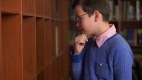 Lo scolaro sveglio sceglie un libro alla lettura in una biblioteca fotografia stock