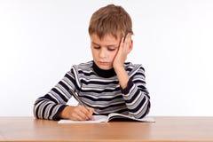 Lo scolaro sveglio sta scrivendo immagine stock