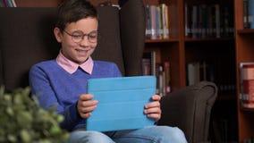 Lo scolaro sveglio utilizza il app sul suo smartphone mentre si siede in una sedia fotografia stock