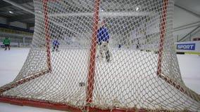 Lo scopo, portiere del bambino manca i dischi di hockey nel portone su addestramento dentro la pista di pattinaggio sul ghiaccio  video d archivio