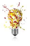 Lo scoppio rosso giallo della pittura ha fatto luce la lampadina Immagini Stock Libere da Diritti