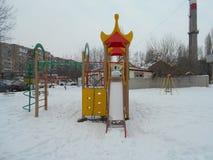 Lo scorrevole dei bambini rossi e gialli in cumulo di neve Immagine Stock