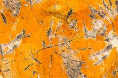 Lo scorrevole rotondo del pezzo di superficie di legno astratto del fondo ha coperto a fiocchi stagionato della pittura arancio fotografie stock libere da diritti