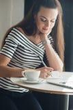 Lo scrittore femminile sorridente sta lavorando con la sua nuova idea al pranzo Donna adulta attraente che si siede alla tavola c Fotografia Stock