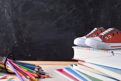 Lo scrittorio con gli strumenti della scuola e la lavagna dispongono a sinistra per il titolo Fotografie Stock Libere da Diritti