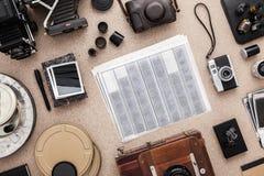 Lo scrittorio del fotografo Macchine fotografiche d'annata, negazioni e rullini Disposizione piana Fotografia Stock