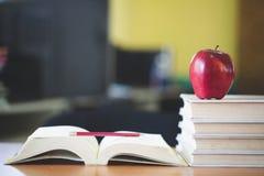 Lo scrittorio del maestro di scuola con la pila di libri e di mela, concetto educativo immagini stock