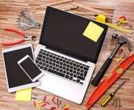 Lo scrittorio del tuttofare di legno nell'alta definizione con il computer portatile, compressa e Fotografie Stock