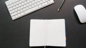 Lo scrittorio dell'area di lavoro con la tastiera ed il taccuino copiano il fondo dello spazio Immagine Stock
