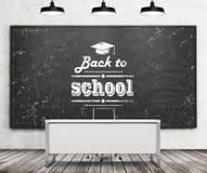 Lo scrittorio dell'insegnante in un'università o in una scuola moderna Una lavagna nera enorme sulla parete con annotato la frase royalty illustrazione gratis