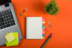 Lo scrittorio della tavola dell'ufficio con l'insieme dei rifornimenti variopinti, il blocco note in bianco bianco, la tazza, la  Fotografie Stock