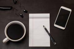 Lo scrittorio nero con caffè in tazza bianca, il taccuino, lo smartphone bianco ed il piano della penna pongono il concetto dell' fotografia stock libera da diritti