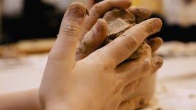 Lo scultore pugging l'argilla per creare le terraglie Immagini Stock