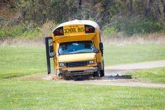 Lo scuolabus che guida nel fango ha attaccato sulla strada Fotografia Stock