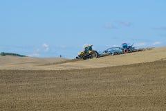 Lo sfidante seguito MT765D del trattore con il trapano di seme pneumatico Lemken Solitair 9 funziona nel campo un giorno soleggia Fotografie Stock Libere da Diritti