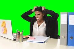 Lo sforzo di sofferenza della donna di affari che lavora all'ufficio ha isolato il fondo verde di chiave dell'intensità fotografia stock