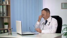 Lo sfregamento stanco di medico osserva, giorno lavorativo duro, cartelle sanitarie di osservazione del computer portatile fotografie stock libere da diritti