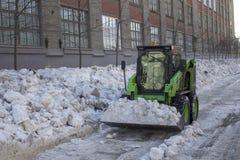 Lo sgombraneve a turbina verde rimuove la neve dalle vie della città fotografia stock