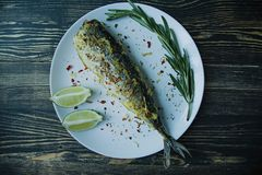 Lo sgombro fritto è servito su un piatto, decorato con le spezie, le erbe e le verdure Nutrizione adeguata Vista da sopra Di legn fotografia stock libera da diritti