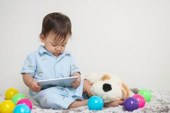 Lo sguardo asiatico sveglio del bambino del primo piano alla compressa a casa su tappeto grigio con la bambola e la parete variop immagine stock libera da diritti