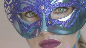 Lo sguardo degli occhi verdi della ragazza misteriosa nella maschera veneziana con arte dell'inverno compone video d archivio
