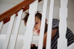 Lo sguardo del ragazzo ha spaventato attraverso il corrimano Fotografie Stock