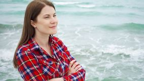 Lo sguardo della donna in mare ondeggia sulla spiaggia Il viaggiatore femminile è freddo durante la vacanza sulla spiaggia a temp archivi video