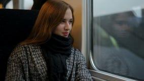 Lo sguardo della donna in treno dell'interno della finestra, pensa e sorride video d archivio