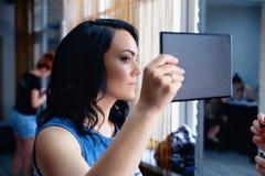 Lo sguardo della ragazza nello specchio e gode del trucco Fotografie Stock Libere da Diritti