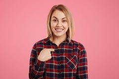 Lo sguardo piacevole sorridente indica a se stessa con il dito, vestito in camicia a quadretti casuale, essendo nel buon umore, e Immagini Stock