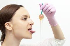 Lo shugaringl matrice della ragazza della depilazione ha immerso la pasta dello zucchero della lecca-lecca per la depilazione immagini stock