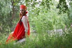 Lo slavo in vestito tradizionale sta sedendosi in natura Fotografie Stock Libere da Diritti