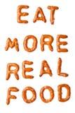 Lo slogan della ciambellina salata dell'alfabeto MANGIA L'ALIMENTO PIÙ REALE isolato Fotografia Stock Libera da Diritti