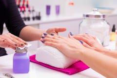 Lo smalto della donna del salone delle unghie rimuove con il tessuto Fotografia Stock