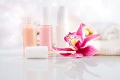 Lo smalto per unghie, gli asciugamani e una singola orchidea fioriscono Fotografia Stock