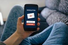 Lo Smart Phone della tenuta della ragazza con sottoscrive il concetto del bollettino su Sc fotografia stock