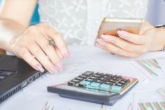 Lo Smart Phone ed il funzionamento della tenuta della mano della donna di affari sul grafico finanziario riferiscono Immagini Stock Libere da Diritti