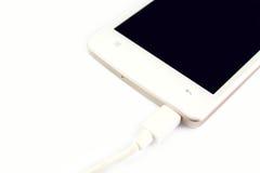 Lo Smart Phone sta facendo pagare su fondo bianco Fotografia Stock