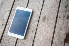 Lo smartphone bianco di colore sopra woodden la tavola Fotografia Stock