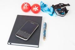Lo smartphone classico di Blackberry e accessoria Fotografia Stock