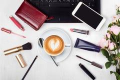 Lo smartphone del telefono cellulare della borsa del cappuccino della tazza di caffè del computer portatile dei cosmetici fiorisc Fotografia Stock
