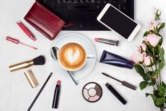 Lo smartphone del telefono cellulare della borsa del cappuccino della tazza di caffè del computer portatile dei cosmetici fiorisc Fotografie Stock