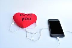lo smartphone ed il trasduttore auricolare con cuore rosso con testo vi amano sul whi Immagine Stock Libera da Diritti