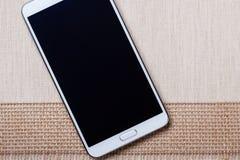 Lo smartphone moderno bianco con lo schermo in bianco si trova sul tessuto Immagini Stock Libere da Diritti