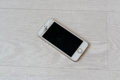 Lo smartphone rotto si trova sul pavimento bianco fotografia stock libera da diritti